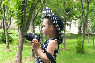 Happy childhood . beautiful childhood .  the advanced child . The girl in a hat from the sun. A hat in peas. Settings of a camera