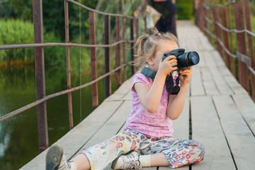 Happy childhood . beautiful childhood . To look in a lens . Old wooden bridge . In the country. Active child .  Evening near the river .  To meet sun dawn . To admire a sunset