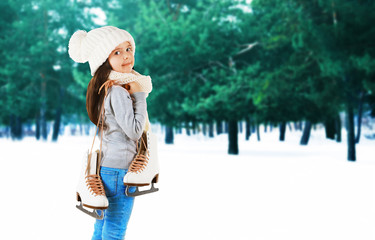 Little girl with skates in trendy knitted clothes on winter forest background