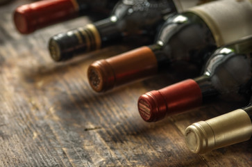 Spoed Foto op Canvas Wijn Row of wine bottles with dry red wine on wooden background. Low depth of field. Wine making and wine shop concept.