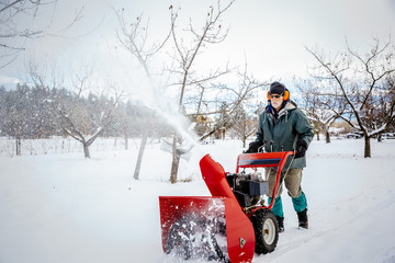 Man using snow blower in snowy field