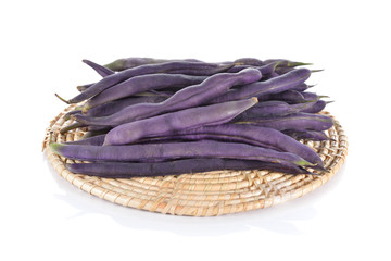 stack of purple beans on rattan tray and white background