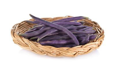 fresh purple beans in rattan basket on white background