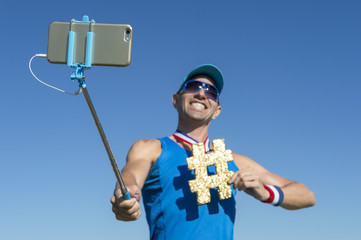 Hashtag gold medal athlete smiling for the camera as poses for a picture with his mobile phone on a selfie stick