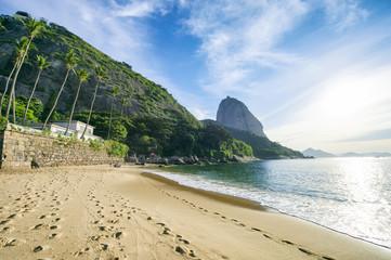 Sugarloaf Pão de Açucar Mountain standing above the quiet shore of Red Beach Praia Vermelha Rio de Janeiro Brazil