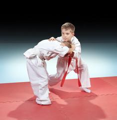 Children in judogi are training capture on gradient background