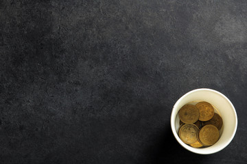 a penny in Cup on black background.The concept of poverty