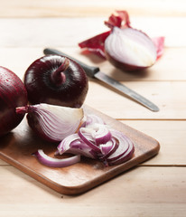Red onion and cutting board on wooden table, selective focus