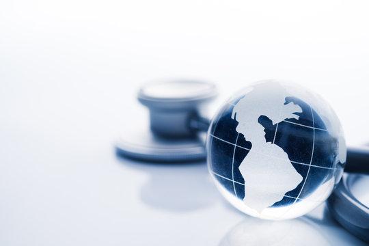 Global healthcare. Globe and stethoscope blue tone on white back
