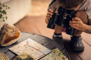 Boy looking through binoculars map on the table