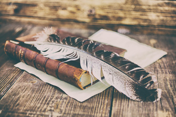 Old book on a wooden background. Quill pen and ink on wooden table.  Vintage toning and background