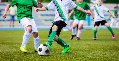 Young Boys Playing Soccer Game on the Professional Football Pitch. Football Soccer Tournament for Youth Teams.