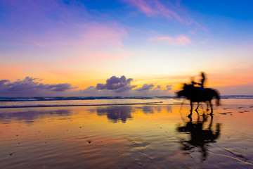 People riding horses at sunset along the beach with a reflection over wet sand and some amazing color in the background.