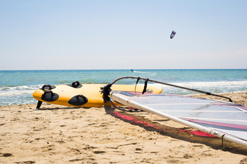 Windsurfing board with sail lying on the sand
