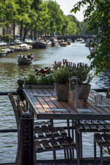 Wooden table with cutlery on the street near the canal in the day in Amsterdam in Europe with several boats as background