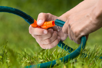 hands connecting hoses for irrigation in the garden
