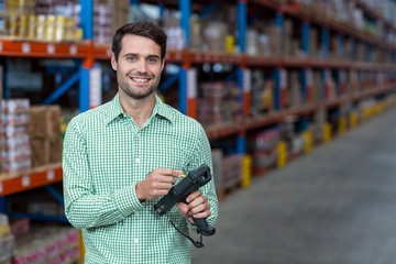 Happy worker holding a tool and smiling
