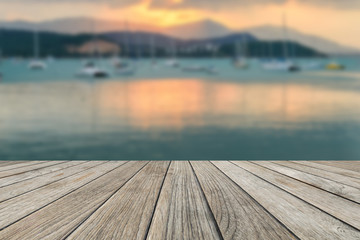 Wood table top with blurred sunset on the beach and sailing boat background