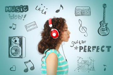 African American woman listening to music in headphones on blue background