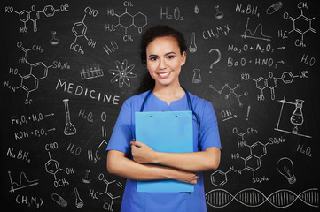 Beautiful African American female doctor on blackboard background