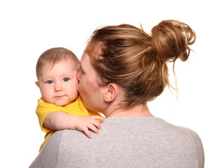 Mother giving baby girl a kiss on the cheek