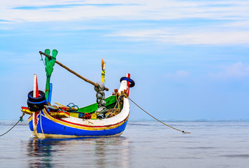 This a traditional style Indonesian fishing boat called a Jukung anchored up just of the shoreline early in the morning.