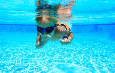 little boy learns swimming underwater