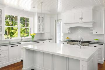 Kitchen Interior in New Luxury Home: White Kitchen with Island, Range, Oven, Hood, Sink, Pendant Lights, Hardwood Floors