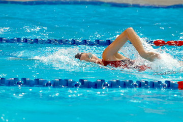 Asian teen swimmer wearing black swimming cap practice forward crawl swimming stroke in a swimming pool for race, side view