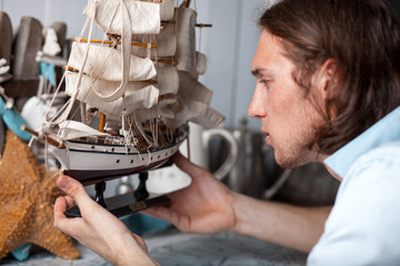 young man looks at model of sailing ship in vintage interior Wall mural