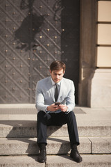 Stylish young businessman talking on the phone outdoors