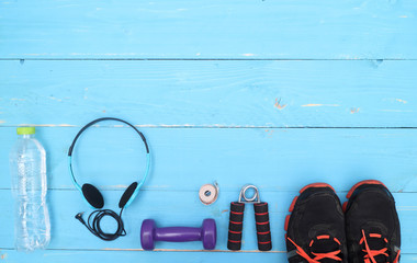 Wall Mural - Flat lay shot of Sport equipment. Sneakers, water, earphones and phone on wooden background. Focus is only on the sneakers.