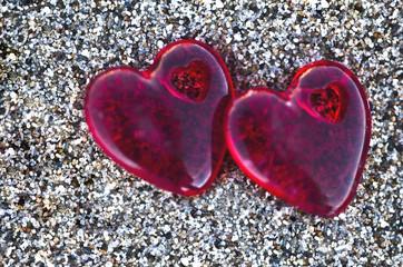 dos corazones rojos sobre la arena de la playa