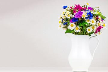 Wildflowers in white ceramic jug.