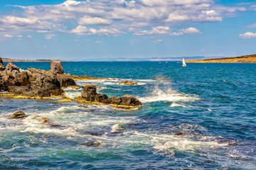 small boat in the sea near rocky shore