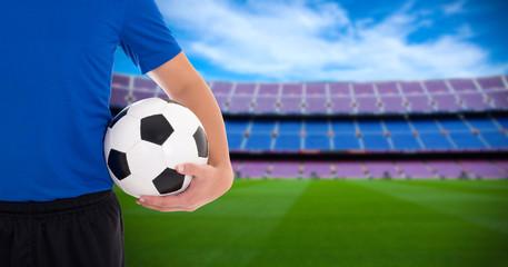 football player holding soccer ball on field of big stadium