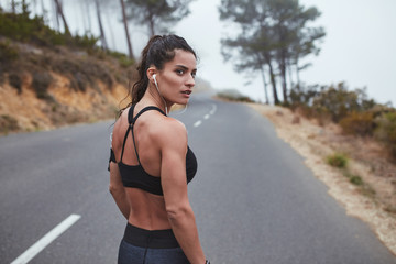 Muscular young woman in sportswear standing on road