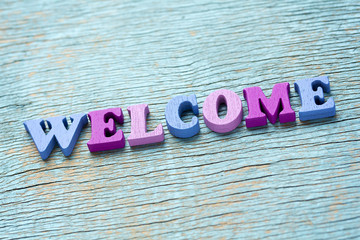 Word welcome on vintage wooden background