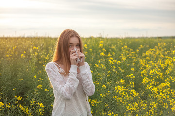 Pollen allergy, girl sneezing in a rapeseed field of flowers