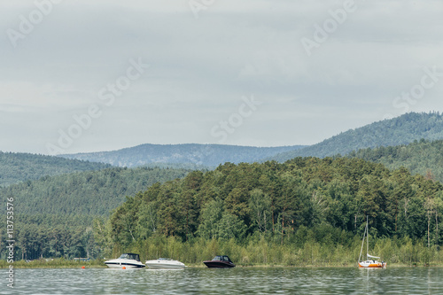 Motor Boats And Yacht Stand At Shore Of Lake On