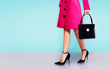 Colorful pink coat woman walking with the leather black purse and high heels shoes. isolated on light blue background