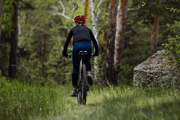 female cyclist riding on a footpath in green grass in forest