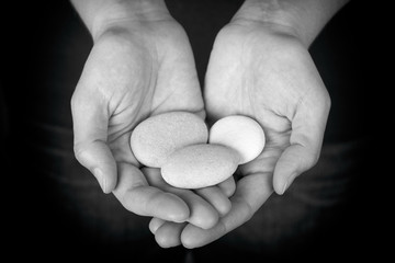 Woman holding three stones in her hands