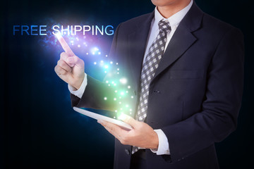Businessman holding tablet with pressing free shipping. internet and networking concept