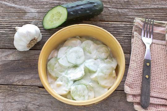 Cucumber salad with cream and garlic in ceramic bowl