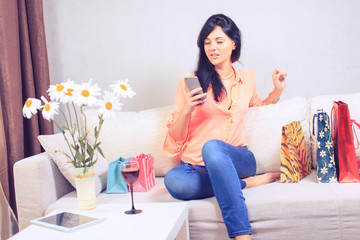 Beautiful young woman holding tablet with shopping bags on sofa