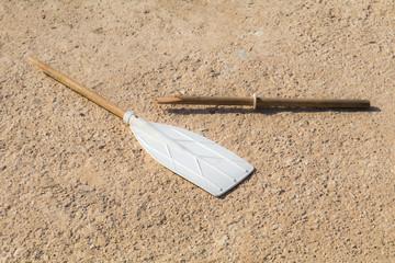 Wooden broken oar, on tan concrete, in the sun.