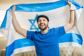 Jewish fan holding the flag of Israel celebrating at home