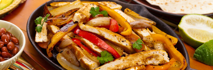 Chicken Fajitas with Grilled Onions and Bell Peppers serve with Tortillas. Selective focus.