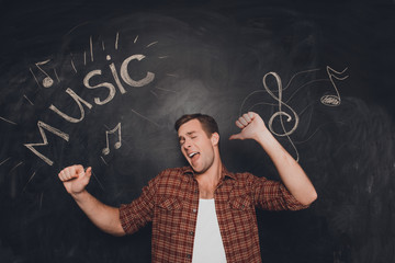 Young pretty musician dancing on the background of blackboard